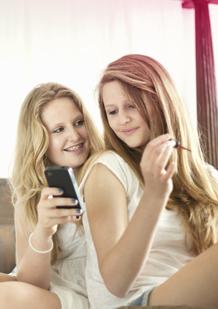 Două fete care vorbesc și se uită pe telefon.